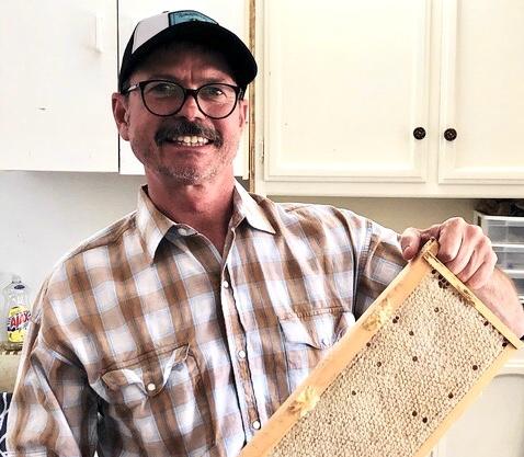 Joc holding a frame of honey